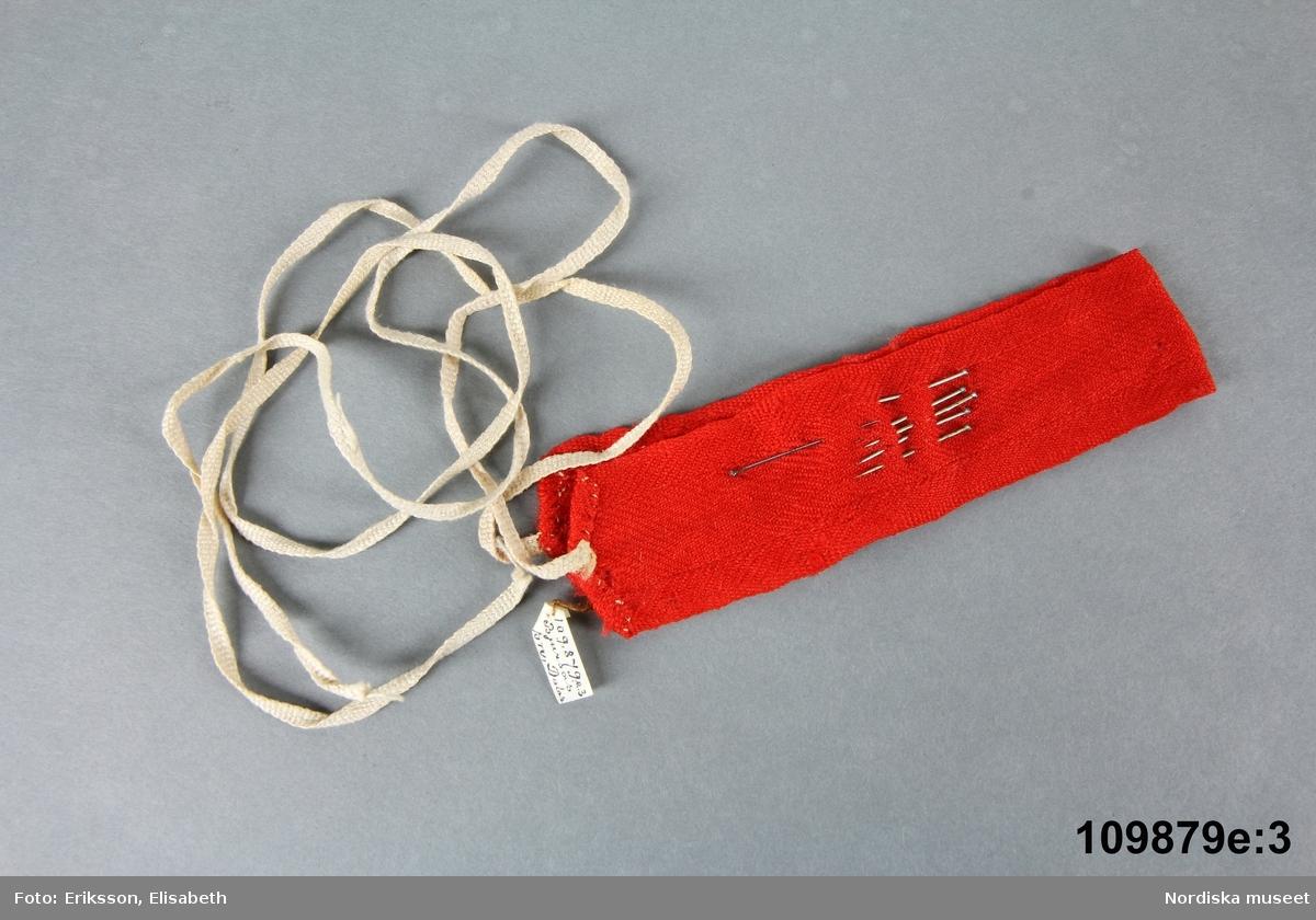 """Huvudliggaren: c: """"Kvinnodräkt bestående av a/ kjol  b/livstycke  c/överdel  d/svart tröja e/ 1-3) hätta med knytning och band,  f/halsduk, rutig  g/halsduk, vit  h/förkläde  j/ 1-2) skor  k/knästrumpor i/kjolsäck""""  Bilaga: Innehåller brev med beskrivning av dräktskicket i Bjursås. Avskrivning finns på excerptkort.     c: Kort överdel av tuskaftat fint hellinnetyg. Rund halsringning,  Liten broderad märkning i vitt lingarn, """" K A"""", plattsöm, i sprundkanten upptill på vänster sida Ärmlinningen har plattsömsbroderier Överdelen är handsydd. Anm: Mycket fläckig. g: Kvadratiskt halskläde av tunt tuskaftat bomullstyg, stärkt, smala handsydda fållar.  h: Förkläde med bröstlapp. Förklädet av vitt tuskaftat bomullstyg, Tygerna är maskinvävda, sömmar handsydda. /Inga-Lill Eliasson 2006-10-16   Kvinnodräkt i 12 delar A. KJOL B. LIVSTYCKE, C. ÖVERDEL D. SVART TRÖJA E 1-3 HÄTTA M. KNYTNING + BAND F. HALSKLÄDE RUTIGT G. HALSKLÄDE VITT H. FÖRKLÄDE I. KJOLVÄSKA längd 28,5 cm, bredd 23 cm J. 1-2 SKOR K. STRUMPOR     i. kjolväska av svart vadmal kantad runtom med röda ylleband. Fickan rikt broderad med stiliserade figurer i övervägande rött, konturerna sydda med rött ullgarn i dubbla rader stjälksöm, figurerna fyllda med flätsöm i tunnare silke i blått, grönt, lila och ljusgult.Baksidan och fickan fodrade med vit bomullslärft. Mönstervävt band i grönt och rött ullgarn på vit linnebotten fastsytt i ena sidan och knäpps med hake och hyska i andra sidan. Kjolväskan är i nyskick.  Berit Eldvik mars 2005"""
