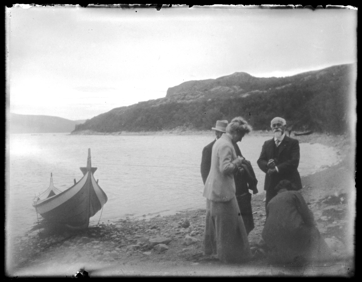 Boris Gleb. En båt fortøyd ved elvebredden. Fire personer på land, det ser ut til at de undersøker noe på stranda