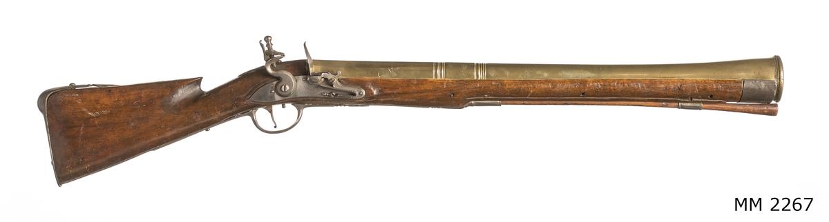 """Muskedunder, större, med trumpetformad mässingspipa och flintlås. 1700-talets förra hälft. Stock och kolv av trä, mekanism och och beslag av järn. Märkning på låsblecket: """"OL:R"""". Finns upptagen på 1761 års inventarium. Pipans längd 730 mm."""