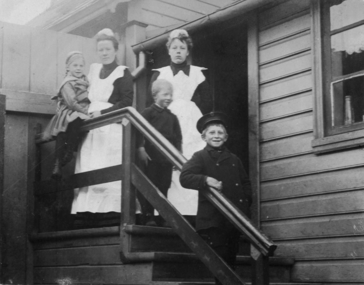 To damer med hvite forkle og skaut på hodet står på en trapp sammens med to gutter og en jente.