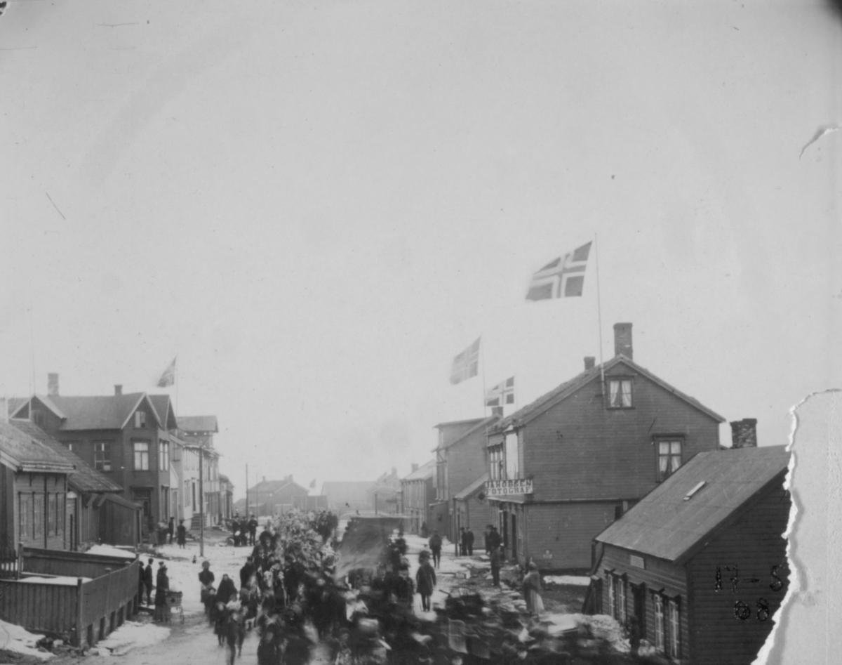 Folk som går i tog. Flagg på husene. Bildet er tatt fra Kr. IVs gt. matr. 35 mot Østervågen og resten av gaten.