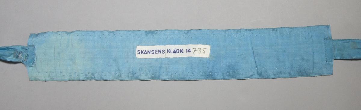 Strumpeband för dam av ljusblått sidenband med blombroderi på vitt ylle. Tyget har taggklippta kanter och fastsytt på ett brett sidenband med kråkspark. På kortsidorna fastsytt smalare sidenband i samma blåa färg.