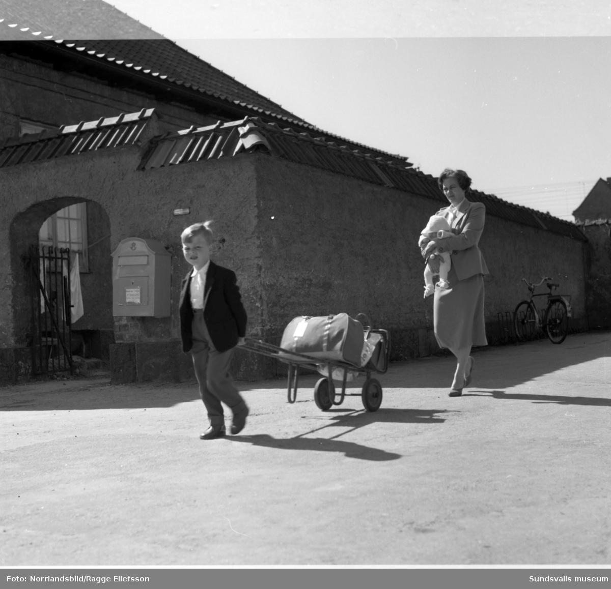 SJ:s paketvagnar för resenärer. En liten pojke drar själv familjens bagage på centralstationen i Sundsvall medan mamma bär på en baby.