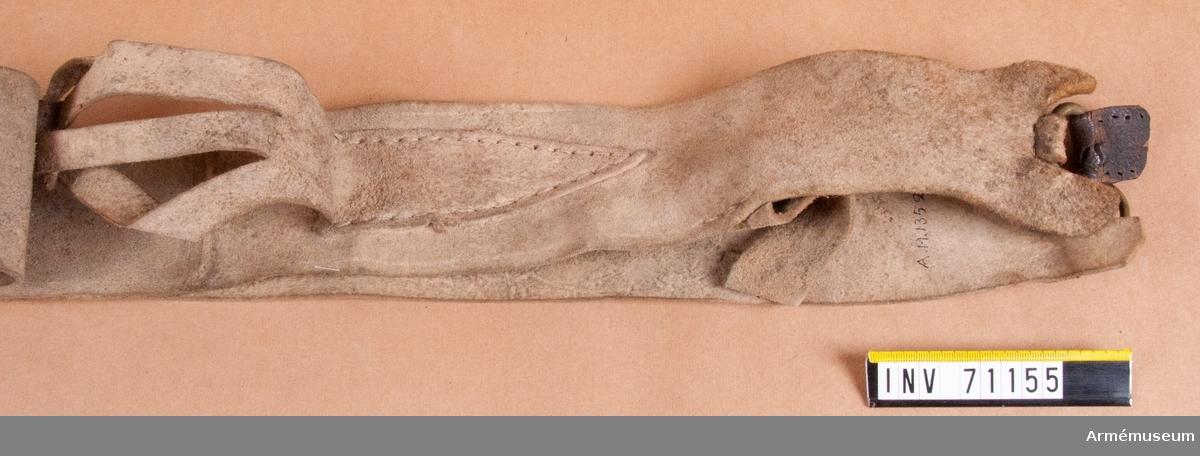 Grupp C:II. Av sämskat läder med rensnål för fänghålet. (Ovanlig typ).  Detta bör vara en bantlärrem till patronväska för infanteriet under Karolinsk tid. Detta baserat på de mindre remmar som är fastsydda på framsidan, vilka skulle fästas vid kruthorn, rymnål m.m.