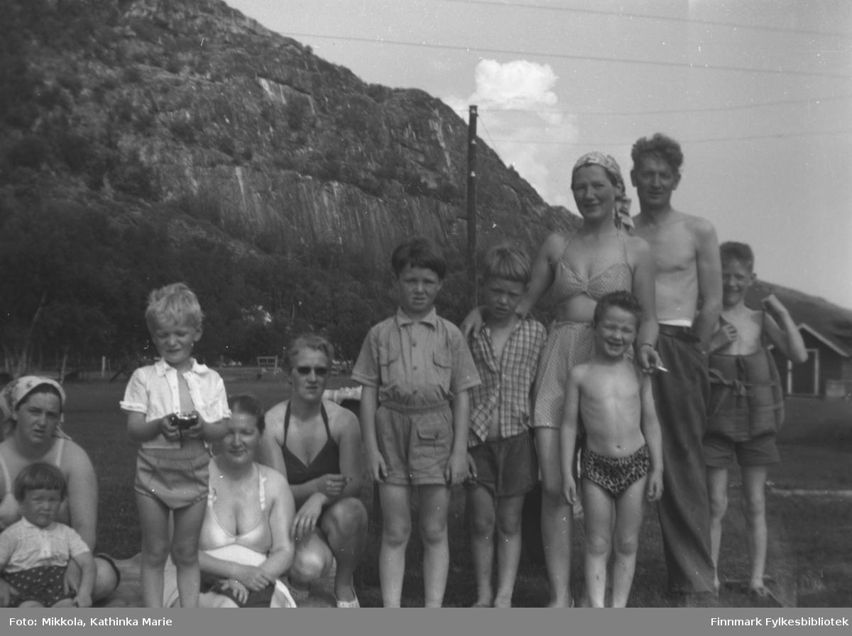 Mikkola-søsknene med barn en fin sommerdag på Mikkelsnes. Alle er lettkledte og flere har badeklær på. Fra venstre: Alfhild Mikkola med datteren Lillian. Sture Olsen Lie, Gudrun Olsen Lie, Herlaug Digre, Roy og Torgeir Mikkola, Kari Havreberg med nevøen Tore foran seg, Mikkel Mikkola og Per Olsen helt til høyre. Per har en slags flytevest på seg. Ut fra barnas alder kan bildet være tatt ca. 1956-1960