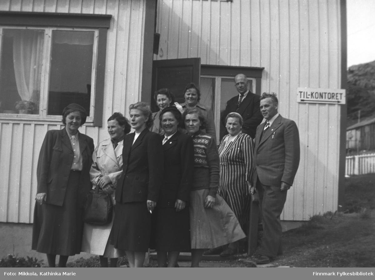 Mange ukjente mennesker samlet til fotografering. Et skilt 'Til kontoret' henger på veggen bak dem. Vi vet ikke hvor bildet er tatt, men antakelig er det i Finnmark et sted. Det kan være tatt i forbindelse med Kathinka Mikkolas engasjement i Neiden helselag