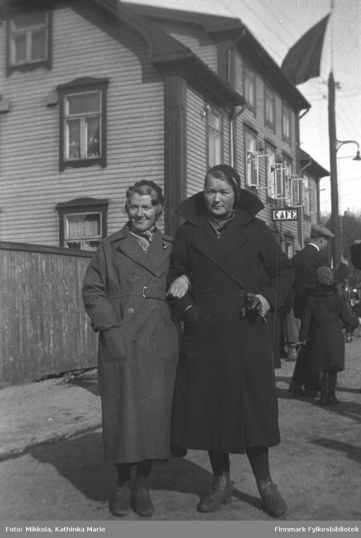 I Kirkenes, ca. 1935-1940. Venninnene Synnøve Mikkola (til venstre) og Gudrun Olsen Lie står utenfor en bygning merket 'Kafe', i bakgrunnen flere mennesker. Et flagg er heist i bakgrunnen, antakelig en rød fane i anledning 1. mai?