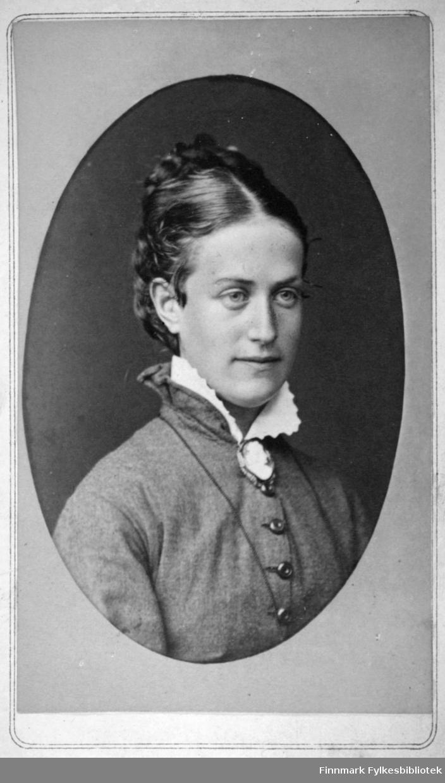 Portrett av en dame i en ganske mørk bluse med store, mørke knapper. Hun har en lys krage med en brosje festet i halsen. Portrettet er tatt hos Marianne Balchen i Steinkjær.