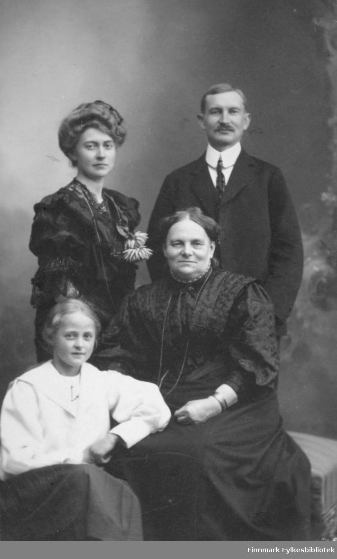 Gruppeportrett av det som sannsynligvis er en familie bestående av mor, far og to døtre. Jenta nede til venstre på bildet har en hvit skjorte/bluse på seg. Den unge kvinnen bak henne er iført en mørk kjole med noe pynt på brystet. Det som sannsynligvis er moren sitter nede til høyre på bildet og har en mørk kjole på seg. Et armband/armbandsur ses på hennes venstre håndledd. Bak til høyre på bildet står en mann i mørk dress, hvit skjorte og slips. Portrettet er tatt hos fotograf Forbech i Christiania.
