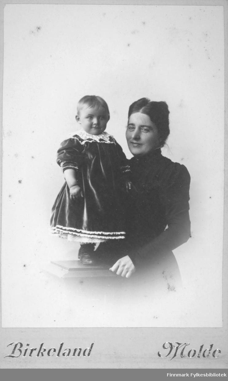 Portrett av en kvinne og et barn. Kvinnen har en mørk overdel på seg. Hun holder armen rundt barnet som står på en søyle og er iført mørk kjole med hvit krage.