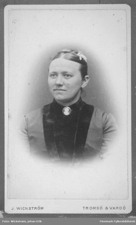 Portrett av en dame. Hun har en ganske lys jakke og et mørkere plagg under. En stor brosje er festet i kragen foran og hun har noe blomster i håret.
