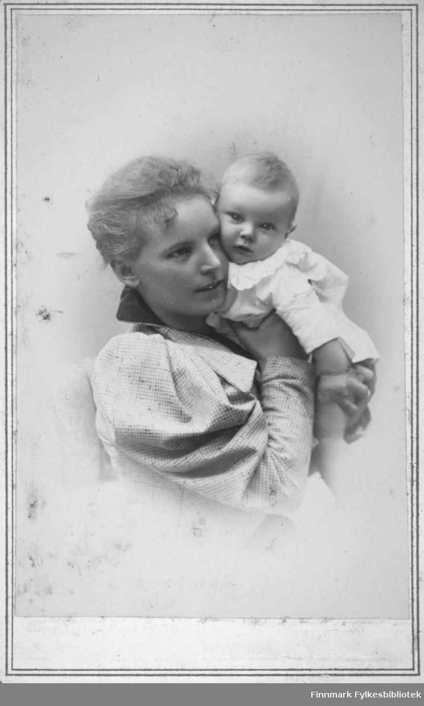 Portrett av en kvinne og et barn, kinn mot kinn. Damen har en lys bluse eller jakke med stor, oppbrettet krage. Barnet hun holder har en lys drakt med blondekrage.