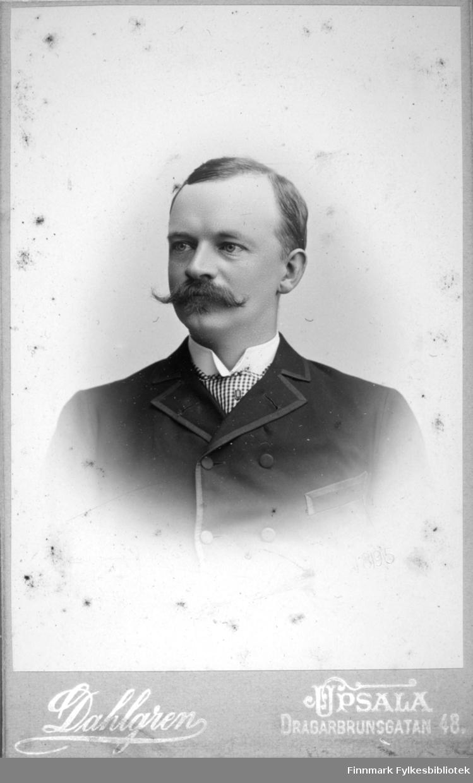 Portrett av en mann iført mørk dressjakke og hvit skjorte. Noe rutet vises i halsen hans, muligens et slips eller vest.