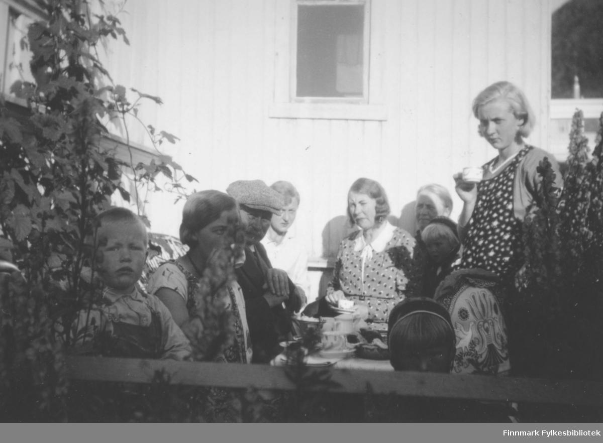 En del personer i varierende alder sitter ved et bord i solveggen. Den unge damen som står har en mønstret kjole og en tynn jakke på seg. Hun har en kopp i høyre hand. Damen som sitter ved veggen har en mønstret kjole med hvit krave på seg. Til høyre for henne ses hodet på et barn. Til venstre for henne sitter en dame som har en hvit kjole på seg. En mann med sixpence på hodet sitter ved langsiden av bordet. En dame og et barn sitter helt til venstre. Noen busker på begge sider av personene og den hvite veggen bak dem har stående panel og to vinduer som vises. På bordet står noen bl.a noen kopper.