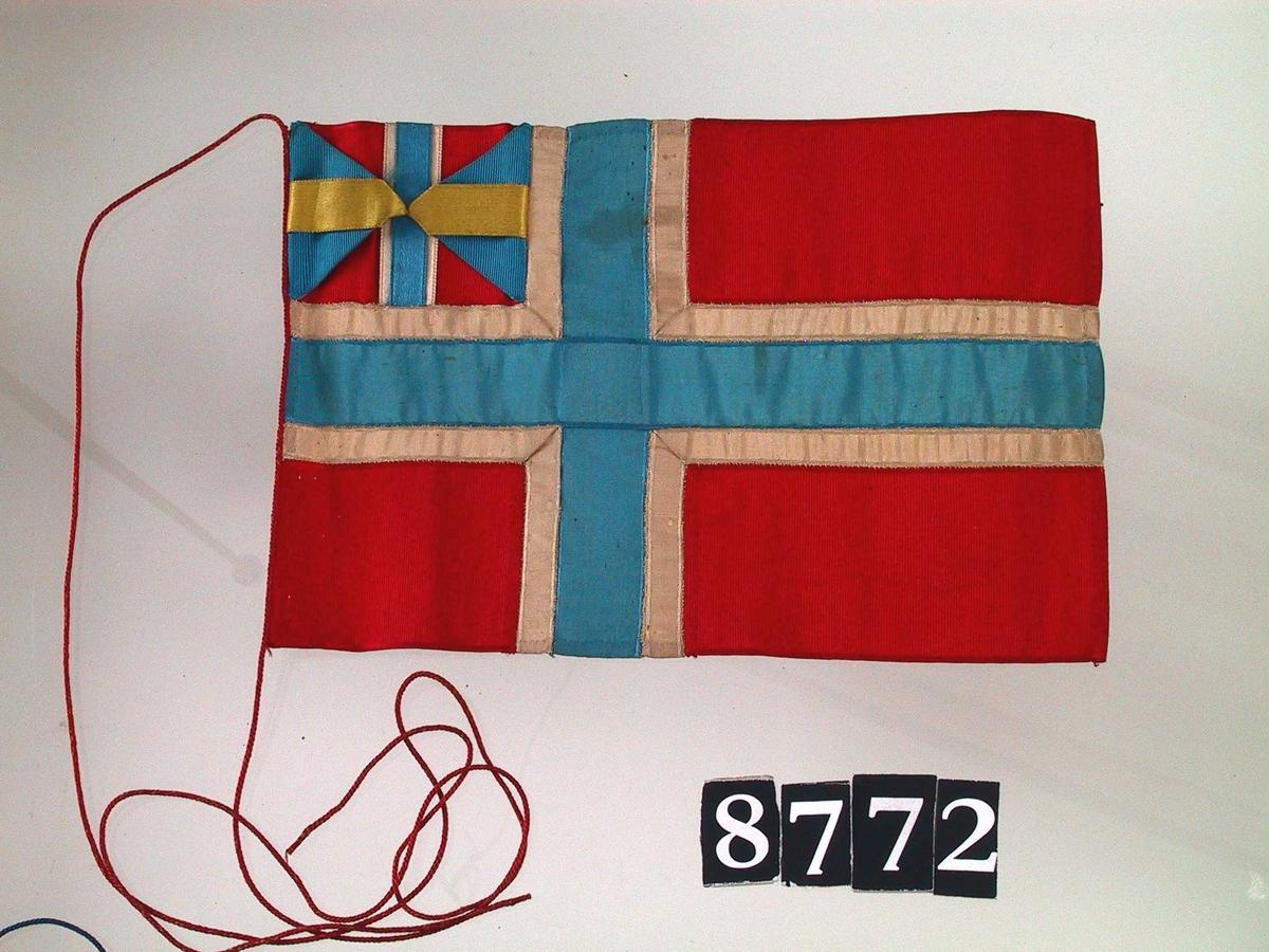 Flaggstang med 7 små flagg, borddekorasjon.    a) Stang. Furu,  med korsformet postament. H. 65,5.    b -h) Silkeflagg,  hvorav fem ca. 16 - 16,5 x 23 - 24.  g) 15,8 x 21,1.   h) belgisk 13x17,7.   Svensk med unionsmerke,  hollandsk,  rødt med Union Jack øverst,   norsk  med unionsmerke,  tysk,  sveitsisk,  belgisk.    Tilstand: bra.