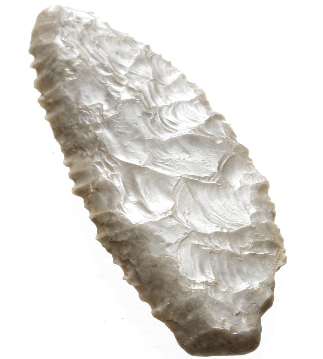 Sigd av lys grå flint. Nærmest som l.c. fig.232, men avviker fra typeeksemplaret ved at den er kortere i forhold til høyden. Sekundært har sigden vært anvendt som ildflint.