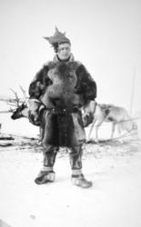 En same står foran to reinsdyr. Han har en stor skinnpesk, s