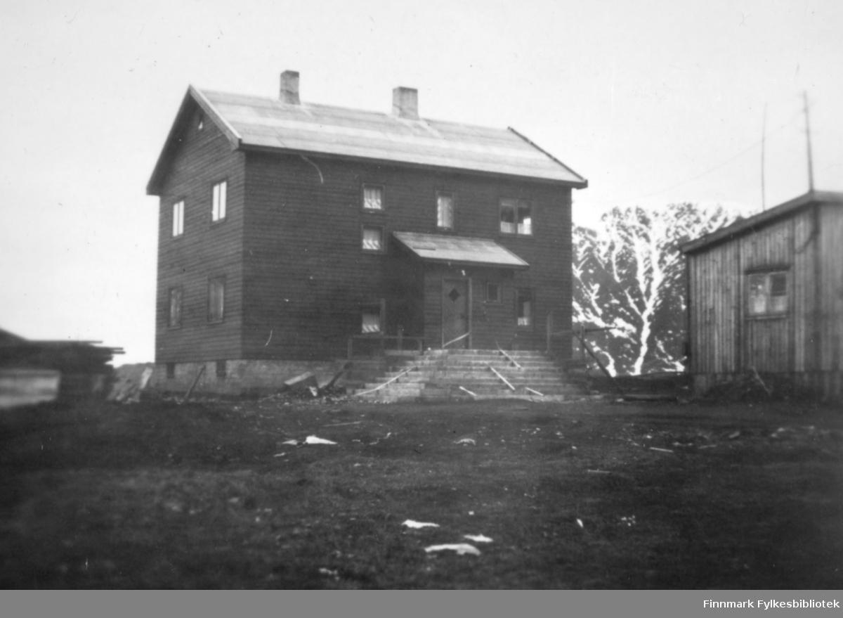 Et stort hus med en bred trapp. Et vindfang står midt på langveggen. Huset er malt med en mørk farge og har vinduer av ulik størrelse på langveggen, og to vinduer på røstveggen. To skorsteiner står på det pappkledte taket. En lav grunnmur har to små vinduer og til venstre for huset ligger en stabel med ved/materialer. Bakken foran huset består stort sett av jord/grus. Til høyre på bildet ses deler av røstveggen på et lite bygg. Det har stående, umalt panel og et sprossevindu som vises på bildet. Et stort fjell ses mellom bygningene. Det er endel snøflekker på det.