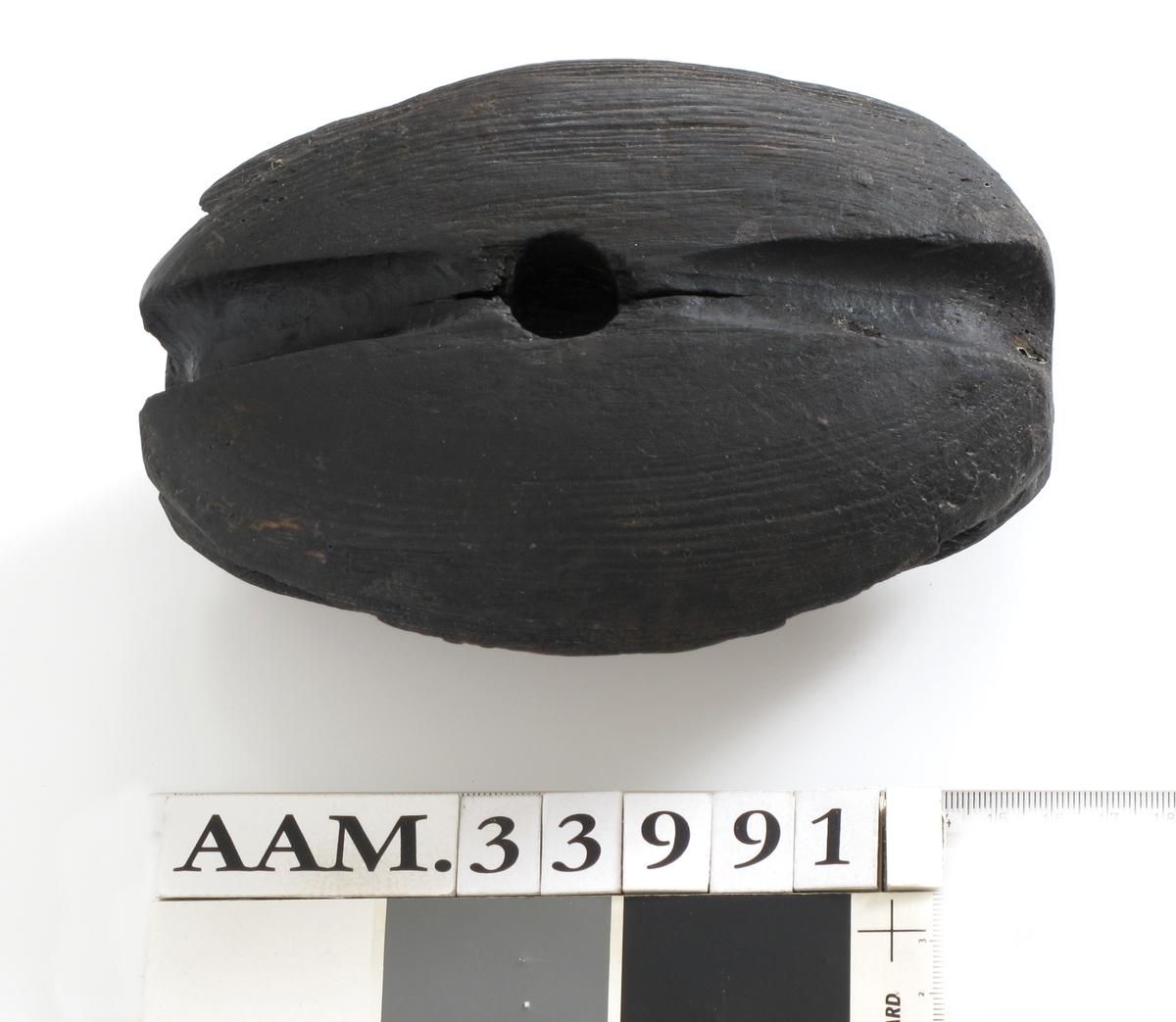 Blokkhus, skåret av ett stykke løvtre, trolig lønn. Mørk farge. Den ene siden er smalere, ser ut til å være tilpasset en spesialfunksjon.