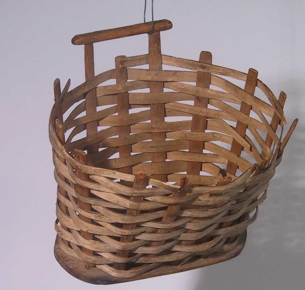 Form: Bunn av oval treplate, fletting med spon rundt flate pinner festet langs bunnens kant. Håndtak øverst på den ene langsiden.