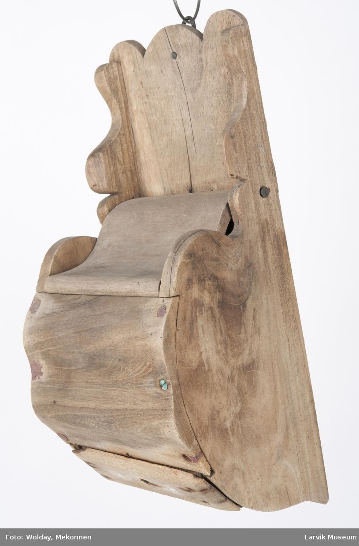 Form: rett rygg og sidestykker skåret i ett stykke.  forstykket buet,festet til sidene med messingstifter buet lokk, festet med messingskruer. nederst skuff med messingknott. sidestykkene og ryggen skåret øverst. messingsring bak på rygg.