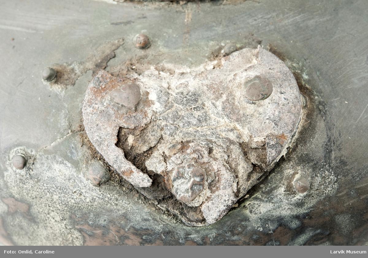 Teknikk: hamret kobber. jernfestene for hanka er naglet fast med kobbernagler (3 på hver side). hanken festet med klinkede kobber- Form: innsiden av lokket dekket av hvitt metall.