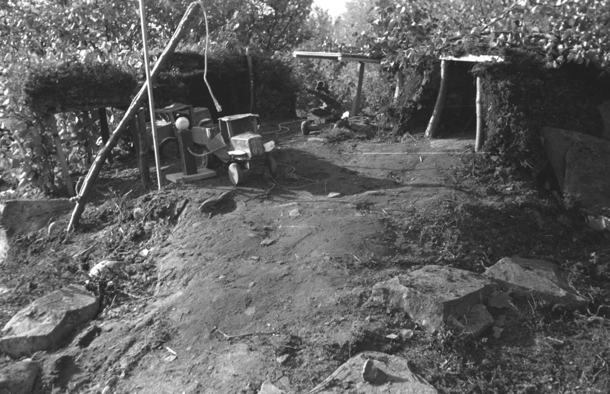 En lekebil og andre saker står utenfor lekehytta til Hauge-brødrene i Andersbyskogen.
