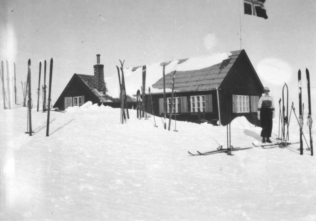 Vinikkahytta. Det er vinter og det ligger snø på bakken. Mange par ski er stukket ned i snøen. Det står en person utenfor hytta. Det norske flagg er heist, oppe på taket
