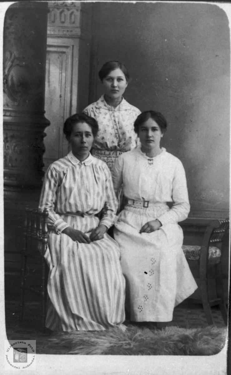 3 unge damer i lyse klær.