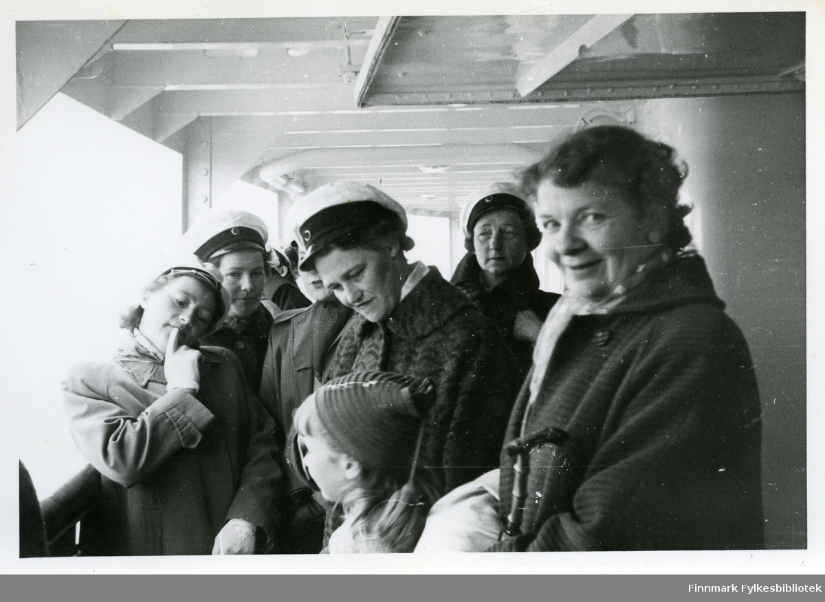 Medlemmer av Vadsø damekor ombord et skip, muligens hurtigruten. Flere av damene har på seg hvite hatter (trolig kor uniform) og kåper. Kvinnen helt til høyre har et sjal rundt halsen. I midten kan man se en jente. Hun har på seg en lue med hengedusk. Kvinnen til venstre har på seg hansker. Kvinnen til høyre ser ut til å holde en gåstokk eller paraply.