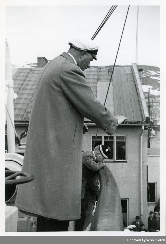 Bildet viser Bugge fra Bjørnvatnet under korstevnet i Honningsvåg pinsen 1956. Han dirigerer trolig et kor. På seg har han en lang jakke og hatt. Bak han kan man se en liten gutt lene seg mot relingen. Gutten har på seg en lue. Bak dem kan man se et hus med vindu og pipe. Enda lenger bak er fjell syndlige.