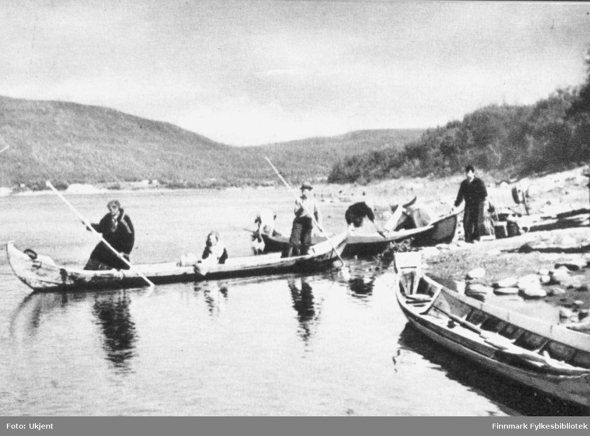 Menn og kvinner ombord en robåt. Kvinnen sitter i midten. Mannen som står framst i båten har på seg kofte. Begge mennene holder på årer. Dette er motivet på et postkort. Det ligger flere båter langs vannkanten. I bakgrunnen kan man se fjell og trær.