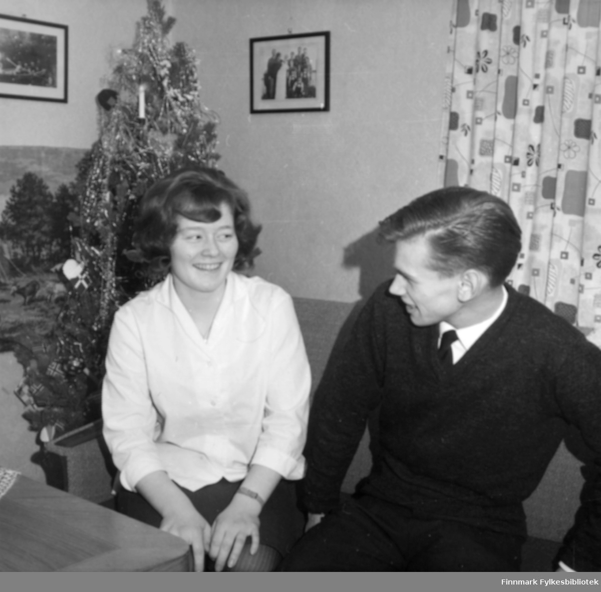 Åse Thomine Ingebrigtsen f. Johansen og Tor Ingebrigtsen som sitter ved siden av hverandre i en sofa i stua på Gamnes. Hun er søster til giver av bildene Karen Kristine Jakobsen f. Johansen. I hjørnet står det et tre med julepynt og lys. Bak sofaen henger det mønstrete gardiner. På veggen er det to innrammede bilder. Åse Thomine er kledt i et kort skjørt, og en hvit bluse. Han har på seg mørk bukse, v-genser, hvit skjorte, og et slips