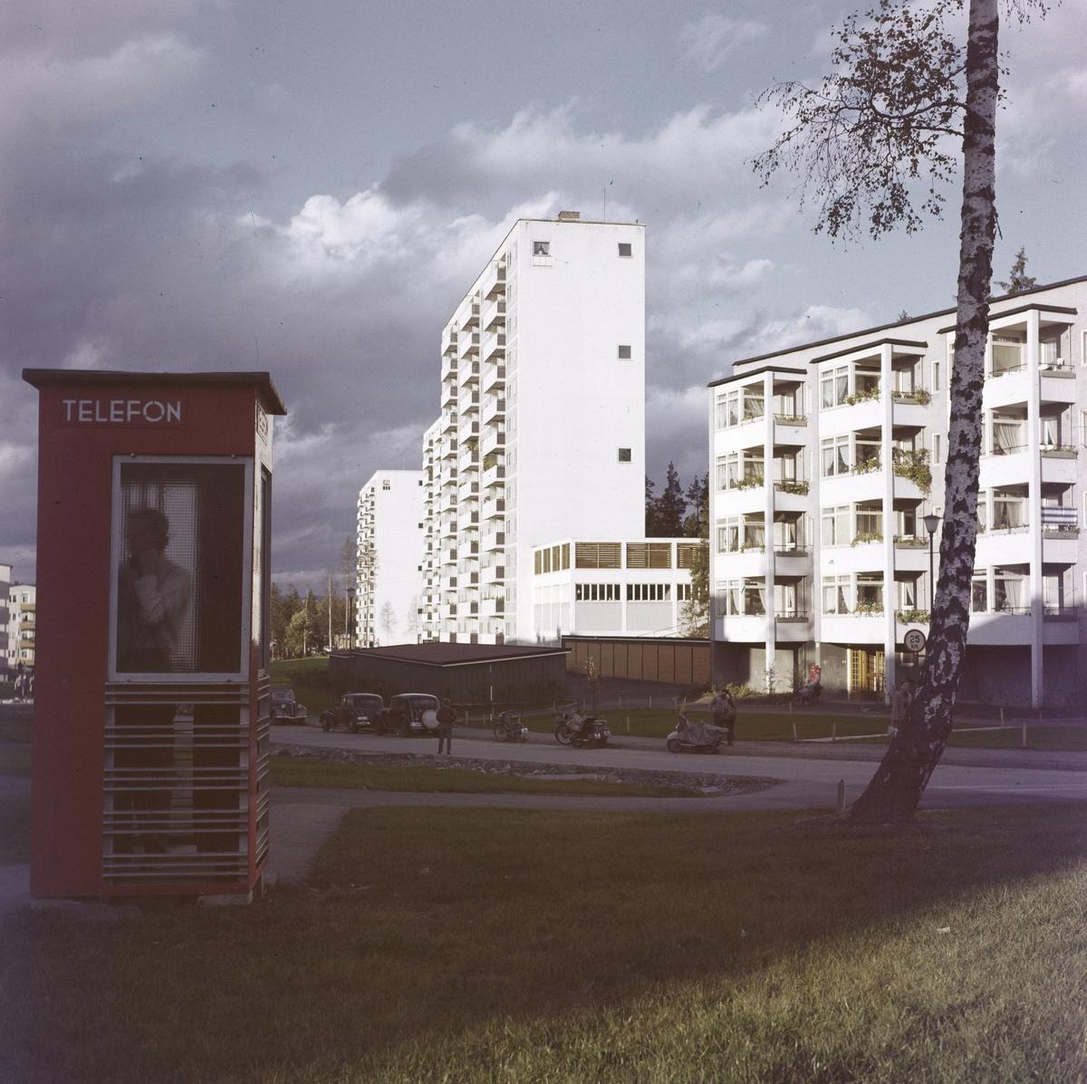 Drabantbyen Bøler med blokkbebyggelse fotografert i oktober 1958. En person snakker i telefonen i en rød telefonkiosk.