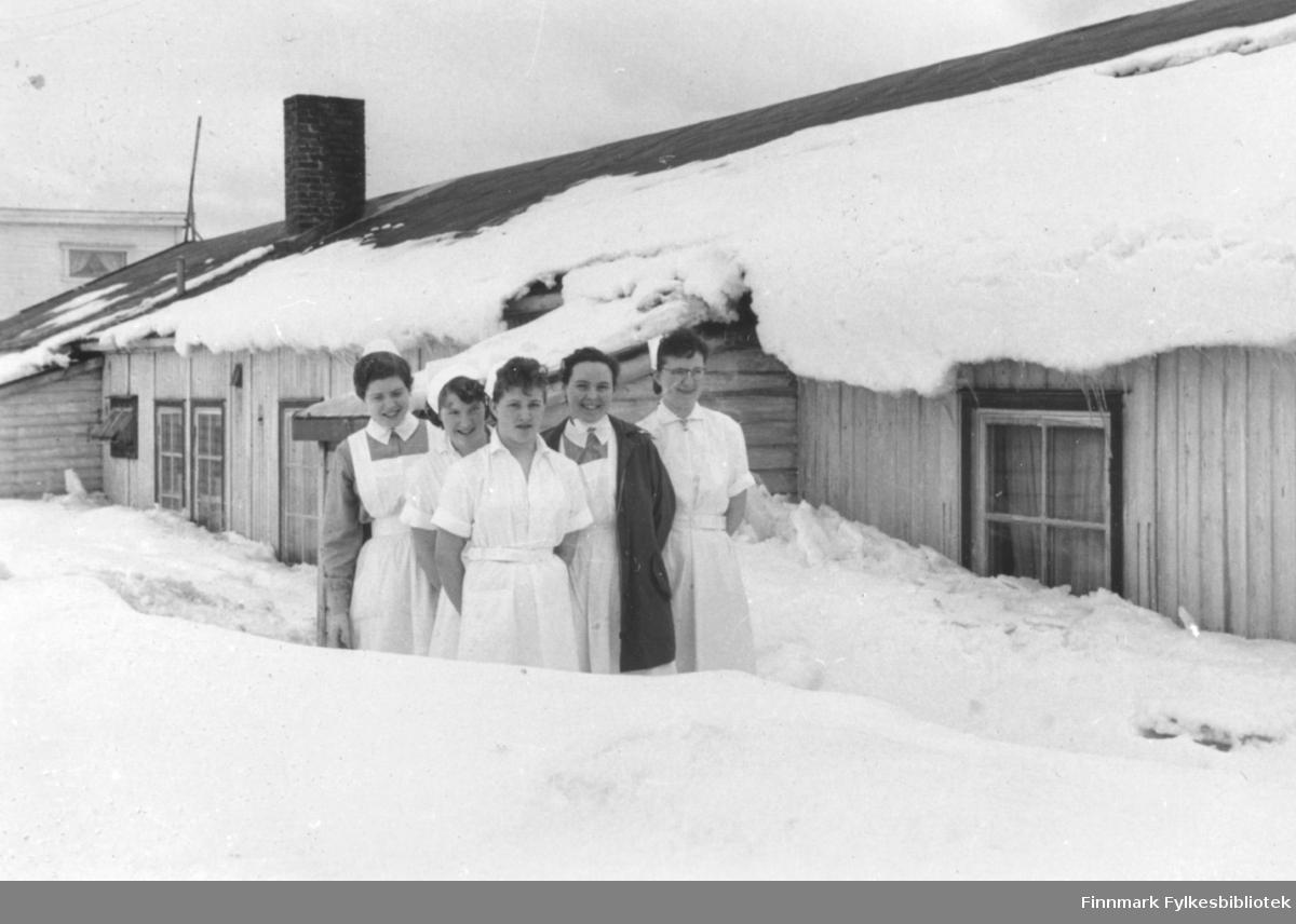 Sykepleiere fotografert i snøen utenfor den gamle søsterbrakka i Amtmannsgate i Vadsø 1958. Fra venstre: Ragnhild Hustadnes Stock, Jorunn Stock, Johanne Johansen, Ruth Ellila, Inger Pettersen