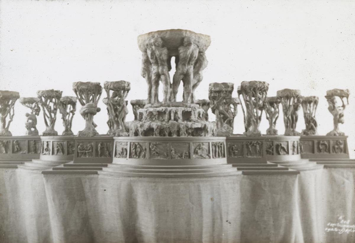 """Dias. Modell av fontene. I 1899 modellerte Vigeland et utkast til en fonteneskulptur med seks menn som bærer en skål med sildrende vann, som han tilbød kommunen i 1900. Fontenen ble de neste årene stilt i bero, men høsten 1906 viste Vigeland en modell i 1/5 størrelse i Kunstindustrimuseet: Midt i et stort basseng seks menn bærende et fat, på karmen 20 grupper av mennesker og trær, og innfelt i karmen en frise med 66 relieffer. Aftenposten skrev: """"Det tør vel nok siges, at aldri har et Kunstverk vakt slik Sensation her hjemme som denne Fontæne."""" Kritikken var stort sett entusiastisk. Det ble dannet en privat innsamlingskomité, og etter at nesten hele beløpet var dekket, bestilte kommunen fontenen til Eidsvolls plass 1907."""