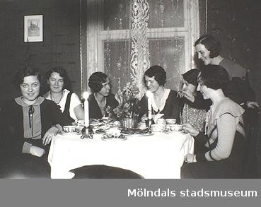 Ur familjen Wallerstedts album. Sju kvinnor sitter runt ett kaffebord med tända ljus.   Dagmar Wallerstedt var handarbetslärarinna och hennes far Artur Wallerstedt var kamrer på Papyrus. Okända personer, 1930-tal.