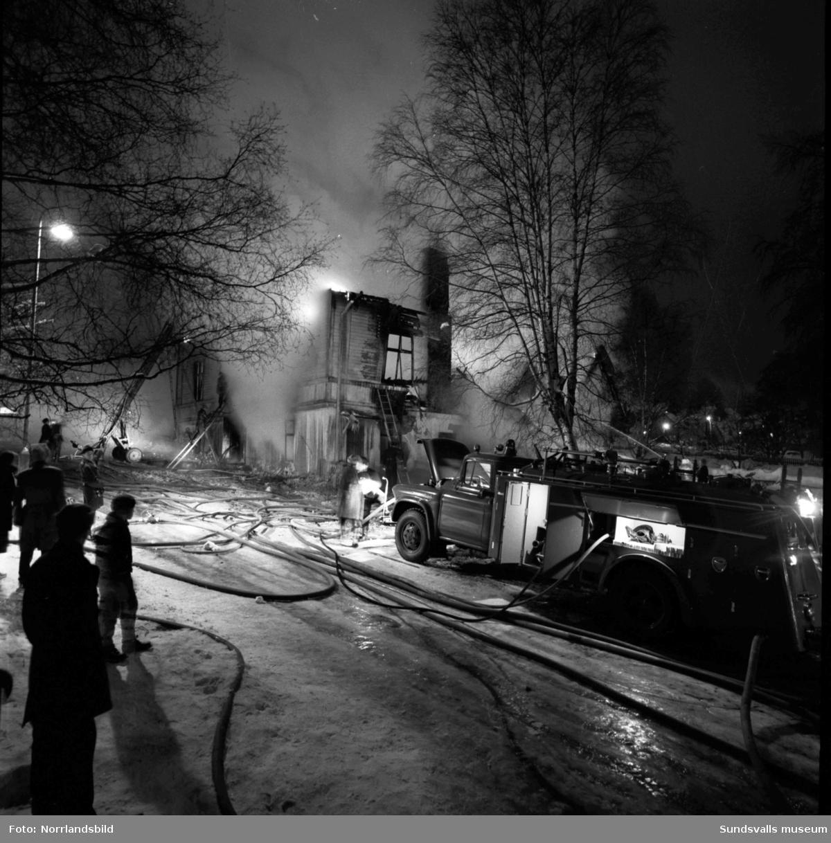 Ett stort trähus vid Nygatan, Skolhusalléns södra ände, på Södermalm brinner och släckningsarbetet pågår mitt i smällkalla vintern.