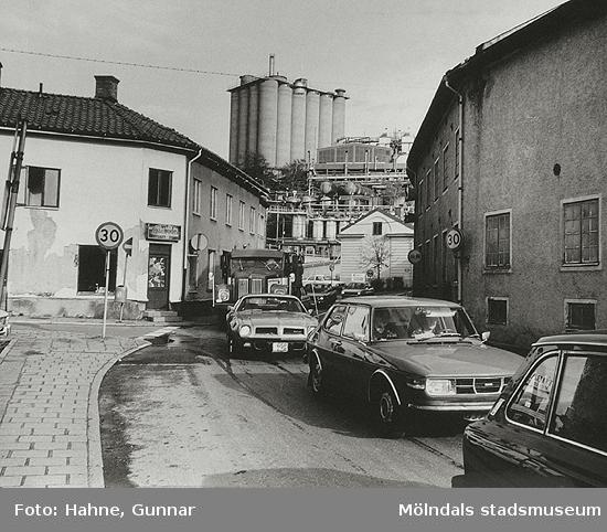 """""""Kråkan"""" är Kvarnbygatans backe. Till vänster ses Malmgrenska huset (Kvarnbygatan 45) samt Götiska Förbundets skola (Kvarnbygatan 49). Till höger ses Soabs gamla fabriksbyggnader mellan Kvarnbygatan och Mölndalsfallen. Soabs höga torn ses i bakgrundens mitt. Cirka 1980."""
