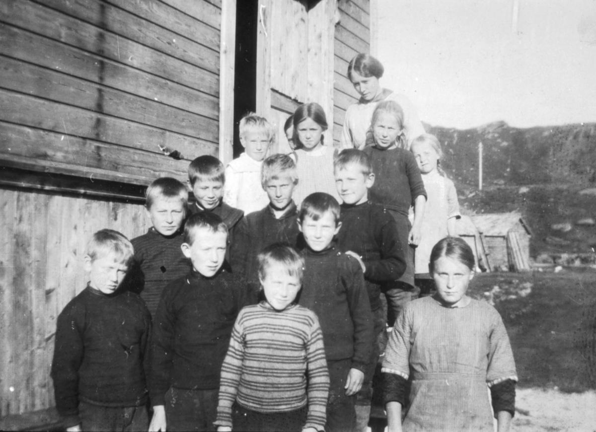 """""""Småskolen. Breivik 1916"""". Barn står på trappen til en skole i Breivik. Jentene er kledd i kjoler. Guttene har på seg gensere. I bakgrunnen kan man se et lite trehus og fjell."""