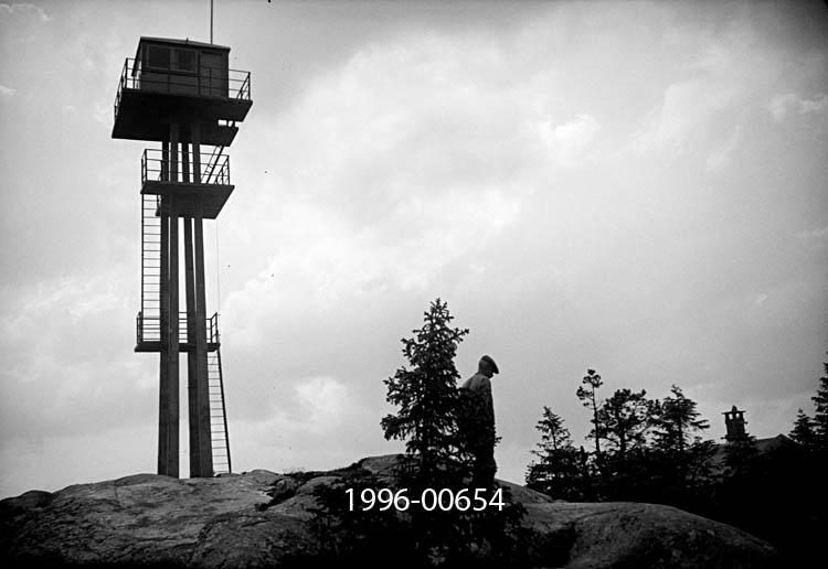Tårnet på Rafjell skogbrannvakstasjon øst for innsjøen Nuguren i Brandval, Hedmark.  Tårnet ligger 585 meter over havet.  Det ble bygd 1934 etter initiativ fra ingeniør Martin Skaare Botner og skogrådet i Brandval kommune.  Da de forela saken for Brandval herredsstyre skrev de med begeistring: «Det norske gjensidige Skogbrandforsikringsselskap har vist planen stor interesse ved å tilby stasjonen opført helt gratis – med telefon, karter, peileapparat o.s.v., men selskapet forlanger sikkerhet for at driften blir ordnet således at stasjonen virkelig holdes besatt i den brandfarlige tid.  A/S Borregaard har også stillet den nødvendige tomt til disposisjon for stasjonen.»  Skogrådet ville gjerne ha et værbestandig anlegg, utført i armert betong, bygd på berggrunn. Det ses til venstre på bildet.  Til høyre for tårnfoten sto en mann og betraktet utsikten.  Framfor ham skimtes et saltak med skorsteinspipe.  Brandval kommune, som seinere er sammenlått med Kongsvinger, eide Rafjellanlegget.  Tårnet var bemannet i tørkeperioder sommerstid og inngikk i den regionale brannberedskapen i regionen fram til og med 1977-sesongen.  Kommunene Brandval, Vinger og Grue bidro til å finansiere dette tilsynet, som i startfasen ble kalkulert til 500 kroner i året.  I 1935-36 ble det laftet ei tømmerhytte like ved tårnet, som overnattingssted for brannvaktene.  Martin og Halvard Østbøl fra Roverud tok byggmesteroppdraget, og igjen betalte forsikringsselskapet Skogbrand kostnadene.  Fra og med 1937 begynte også Luftvernregimentet å bruke anlegget.  Den militære bruken ble fortsatt av Luftkommando Østlandet etter 2. verdenskrig, og de hytta ble modernisert i 1959-1960 delte Skogbrand og de militære brukerne utgiftene.  Fra og med 1978 overtok småflyentusiaster skogbranntilsynet.  Vakthytta ble ødelagt ved en brann i 1982.  Femten år seinere fikk Hokåsen utmarkslag laftet ei ny hytte med tanke på friluftsfolk som har Rafjellet som turmål.  Etter at skogbrannvaktholdet fra Rafjellet oppførte fikk