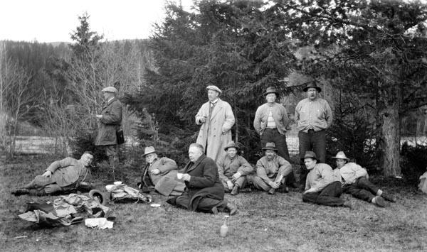 Direksjonen i Christiania Tømmerdirektion (seinere Glomma fellesfløtingsforening) på befaring langs vassdraget i 1927.  Her er de samlet på ei grasslette i Stor-Elvdal, antakelig i nærheten av elva Søkkundas utløp på Glommas vestside litt sør for Rasta.  Dem menn fra fløtingsstyret nyter kaffe, to i stående posisjon og tre i hvilende posisjoner på bakken, til venstre i bildet.  Disse mennene skiller seg, med sine frakker og dresser, tydelig fra de busserullklede fløterne til høyre i bildet.  Blant fløterne synes vi å dra kjensel på Thorvald Øyen og Kristian Øyen, stående bakerst til høyre på bildet.