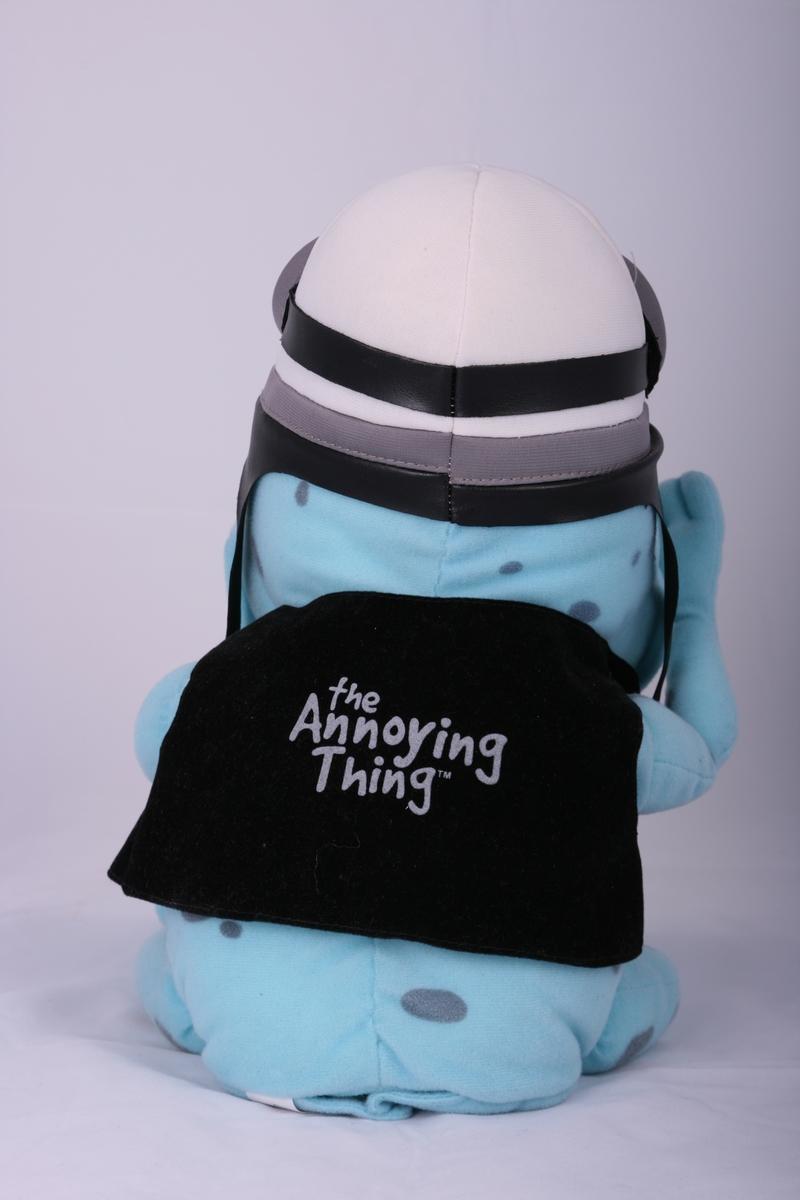 Leketøy med elektronisk lydspor. Dukken skal være en frosk. Frosken har på seg lue, briller og vest. Ved å trykke på foten starter sangen å spille. Armene kan bevege seg. På undersiden, rumpen, kan det åpnes en klaff hvor man kan sette inn batterier.