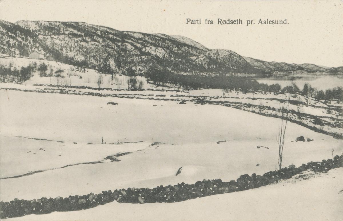 Steingarder i vinterlandskap på Rødset i Ålesund kommune. Brusdalsvatnet og en gård i bakgrunnen.