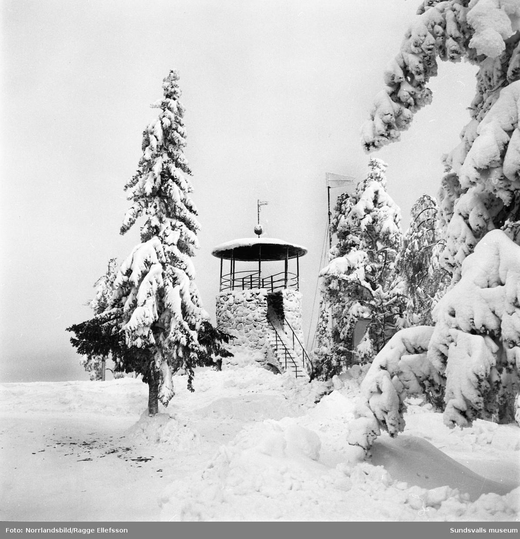 Vinterbilder från Södra berget, två män framför det gamla utkikstornet.