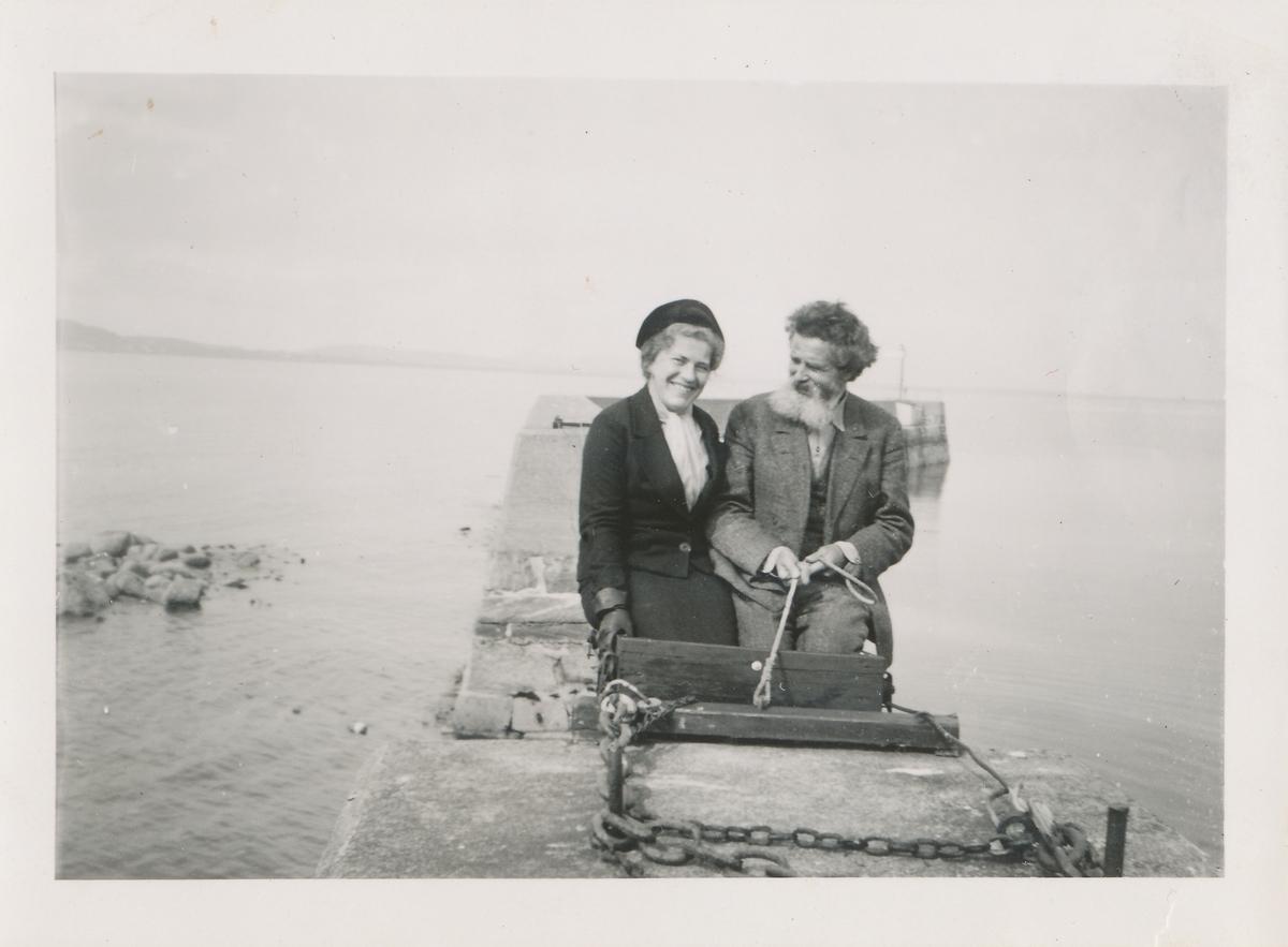 En mann og kvinne sitter på en molo ved sjøen.