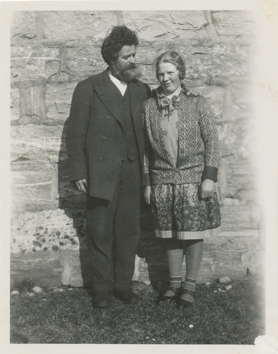En mann og kvinne poserer foran en steinmur.