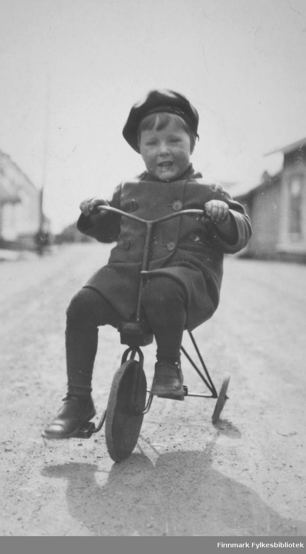 En ukjent gutt på trehjulsykkel. Stedet er også ukjent, men kan være Vadsø.
