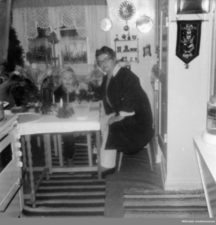"""Anna """"ve sjön"""" (Anna Johansson) och broderns barnbarn Lars-Åke, 4 år, sitter vid ett köksbord 27 december 1972. Anna arbetade på Gunnebo slott."""