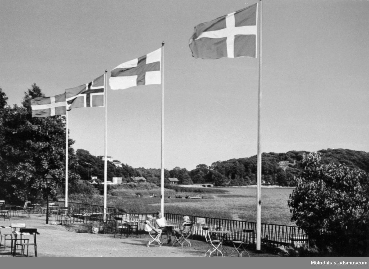Vykort som visar de nordiska ländernas flaggor (förutom Islands) vid Stensjöns strandservering, 1970-tal. I bakgrunden Gunnebobro.